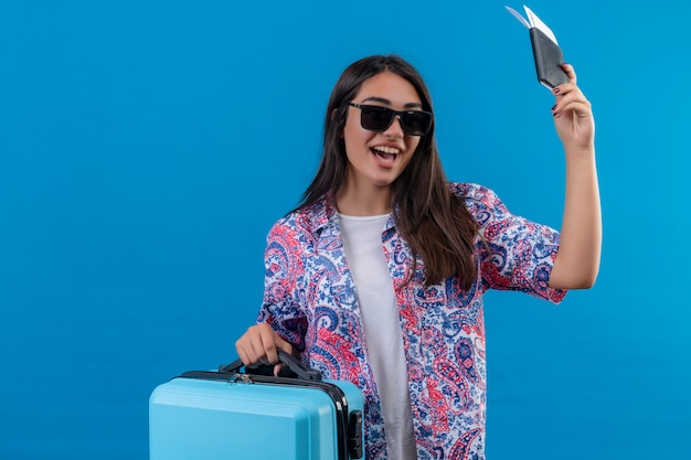 Pleased young beautiful traveler woman wearing sunglasses holding blue suitcase and tickets smiling cheerfully with happy face standing over blue background