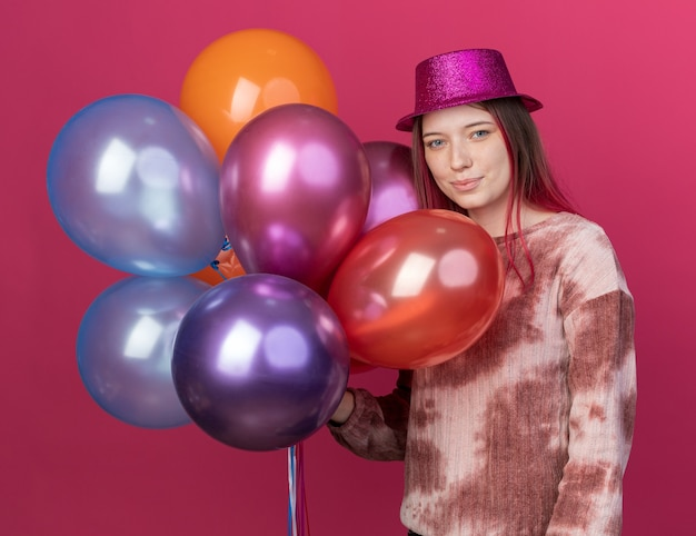 Pleased young beautiful wearing party hat holding balloons isolated on pink wall