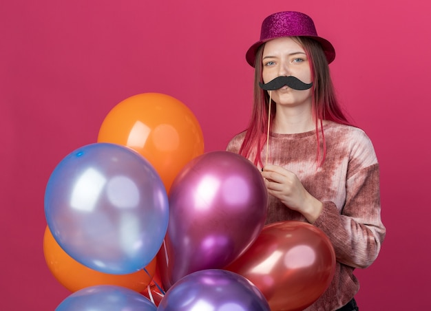 Pleased young beautiful wearing party hat holding balloons with fake mustache on stick