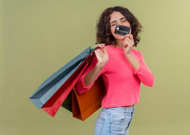 격리 된 녹색 벽에 판지 가방과 카드를 들고 기쁘게 젊은 아름 다운 여자