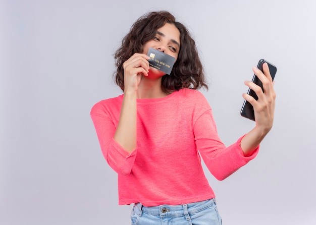 携帯電話を保持していると孤立した白い壁の口にカードを入れて満足している若い美しい女性