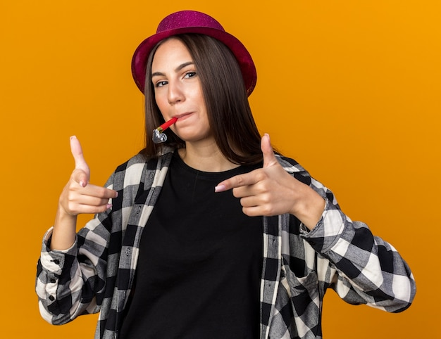 Lieta giovane bella donna che indossa il cappello da festa che soffia fischio di partito punti nella parte anteriore