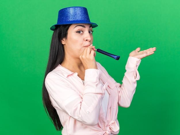 緑の壁に分離された手を広げてパーティー笛を吹くパーティー帽子をかぶって喜んで若い美しい女性