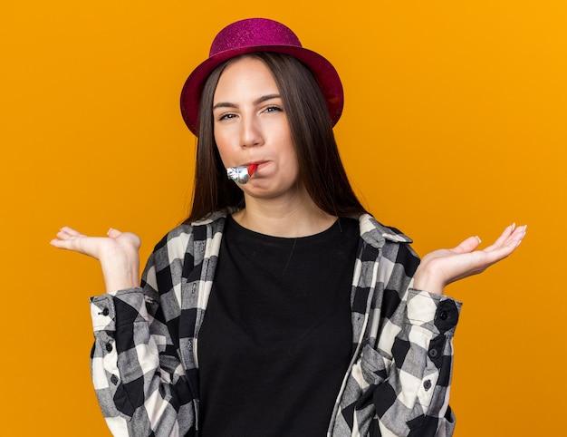 Felice giovane bella donna che indossa cappello da festa che soffia fischio di festa allargando le mani