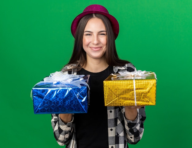 Pleased young beautiful woman wearing party hat holding out gift boxes at front isolated on green wall