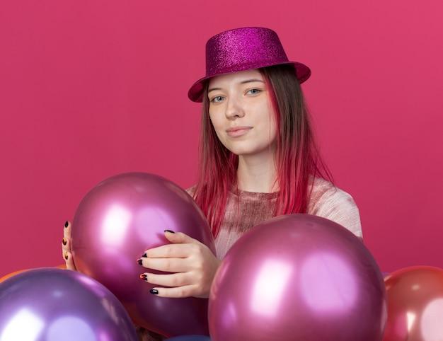 ピンクの壁に分離された風船の後ろに立っているパーティーハットを身に着けている若い美しい女性を喜ばせる