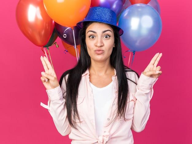 Piacevole giovane bella donna che indossa un cappello da festa in piedi di fronte a palloncini punti su diversi lati isolati su parete rosa