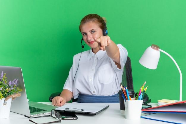緑の壁に隔離されたカメラを見て、指している作業ツールで机に座っているヘッドセットを身に着けている若い金髪のコールセンターの女の子を喜ばせる
