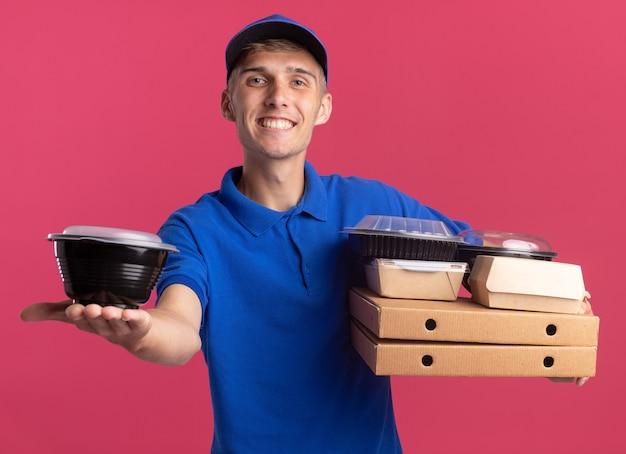 Довольный молодой блондин курьер держит контейнеры для еды и пакеты на коробках для пиццы, изолированных на розовой стене с копией пространства