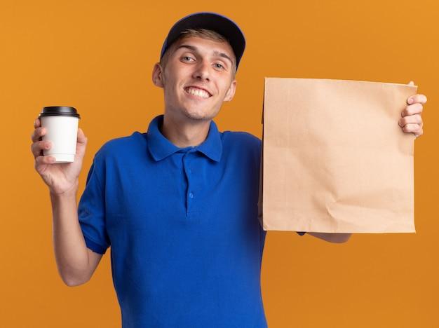 Довольный молодой блондин посыльный, держащий бумажный пакет и чашку, изолированные на оранжевой стене с копией пространства
