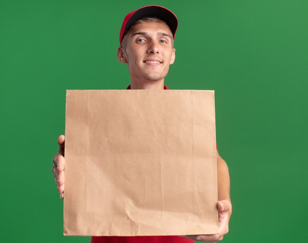 Pleased young blonde delivery boy holding paper package on green