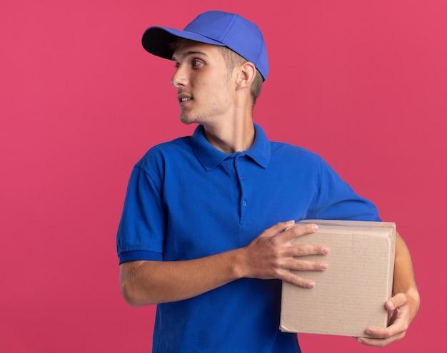 Довольный молодой блондин доставки мальчик держит картонную коробку и смотрит в сторону