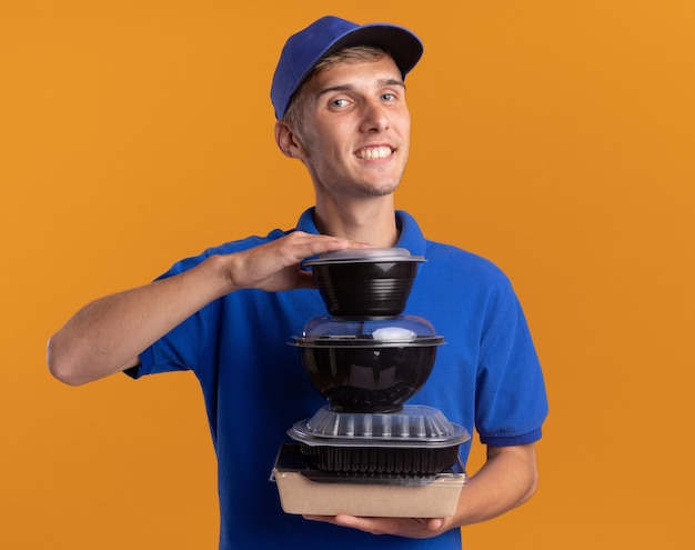 Pleased young blonde delivery boy holds food containers on food package isolated on orange wall with copy space