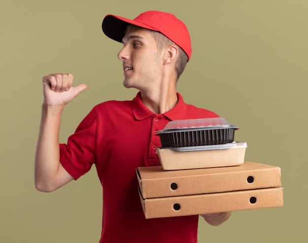 Il giovane ragazzo biondo e soddisfatto delle consegne tiene i pacchetti di cibo sulle scatole della pizza e punta sul verde oliva