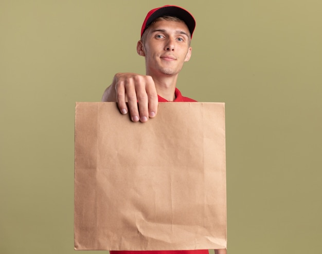Pleased young blonde delivery boy holds out paper package isolated on olive green wall with copy space