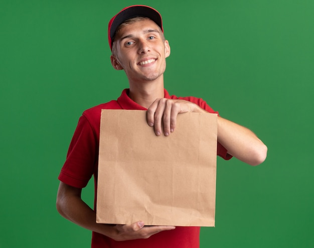 Pleased young blonde delivery boy holds paper package