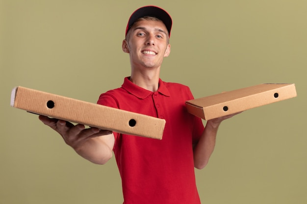 Il giovane ragazzo di consegna biondo piacevole tiene le scatole di pizza sulle mani isolate sulla parete verde oliva con lo spazio della copia
