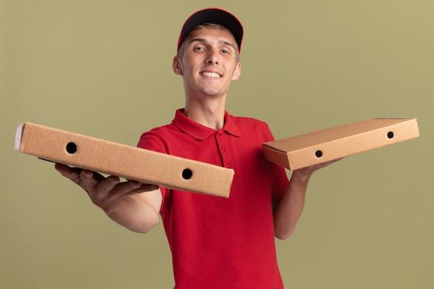 Довольный молодой блондин посыльный держит коробки для пиццы на руках, изолированные на оливково-зеленой стене с копией пространства