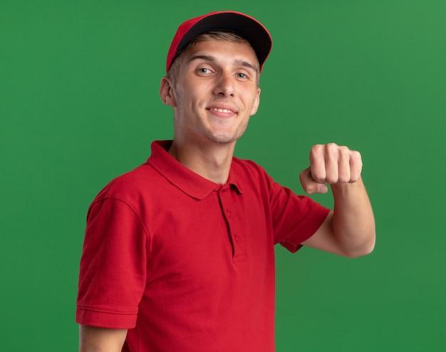 Il giovane ragazzo di consegna biondo piacevole tiene il pugno ed è isolato sulla parete verde con lo spazio della copia
