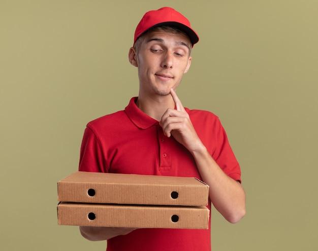 Il giovane ragazzo delle consegne biondo contento mette il dito sul mento tenendo e guardando le scatole della pizza
