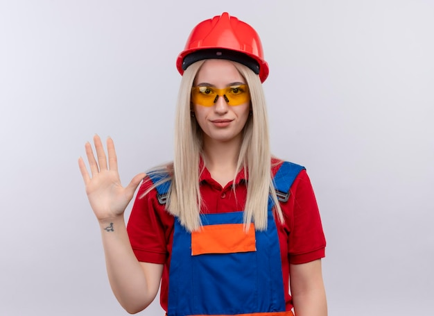 Pleased young blonde engineer builder girl in uniform wearing safety glasses gesturing hi on isolated white space