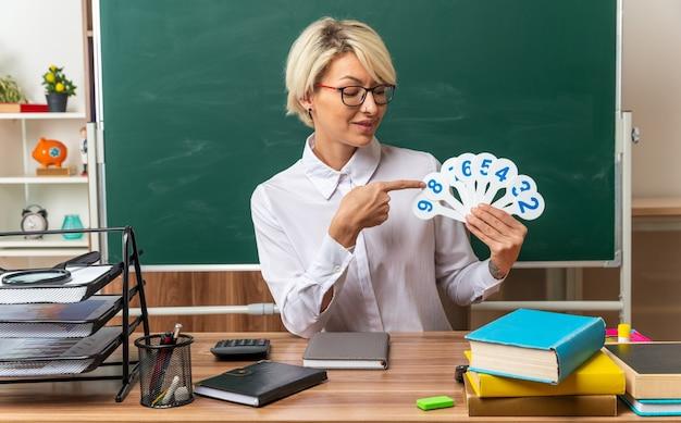 教室で学用品を見せて机に座って眼鏡をかけている若い金髪の女教師を喜ばせ、それらを見ている数のファンを指しています