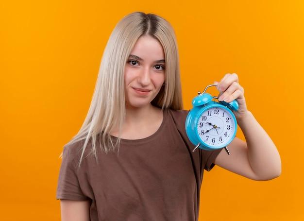 コピースペースで孤立したオレンジ色のスペースを見てハートサインをしている若いブロンドの女の子を喜ば