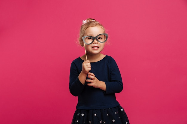 Pleased young blonde girl using paper eyeglasses and looking at the camera over pink wall