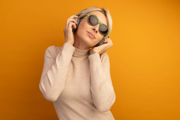 Pleased young blonde girl wearing sunglasses and headphones grabbing headphones listening to music