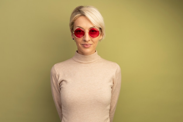 Pleased young blonde girl wearing sunglasses keeping hands behind back isolated on olive green wall with copy space