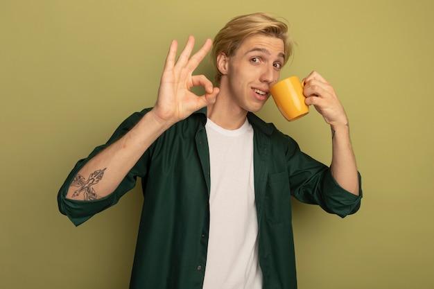 Довольный молодой блондин в зеленой футболке пьет чай и показывает хороший жест