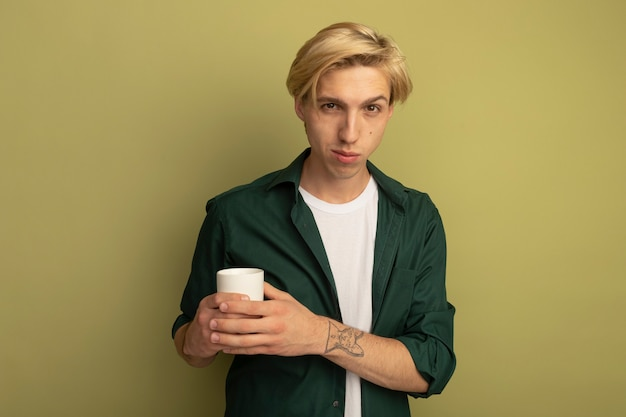 Pleased young blonde guy wearing green t-shirt holding cup of tea crossing hands