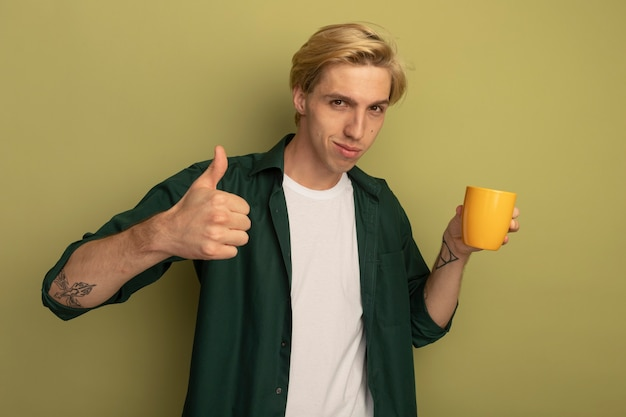 Pleased young blonde guy wearing green t-shirt holding cup of tea and showing thumb up