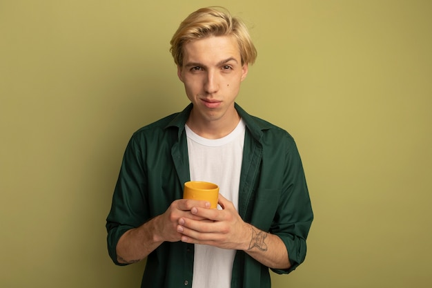 Pleased young blonde guy wearing green t-shirt holding cup of tea