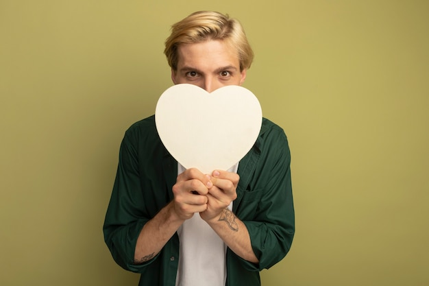Pleased young blonde guy wearing green t-shirt holding heart shape box