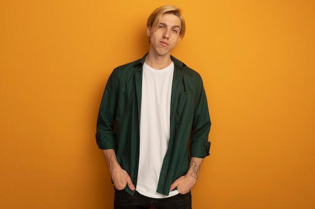 Довольный молодой блондин в зеленой футболке, засовывая руки в карманы