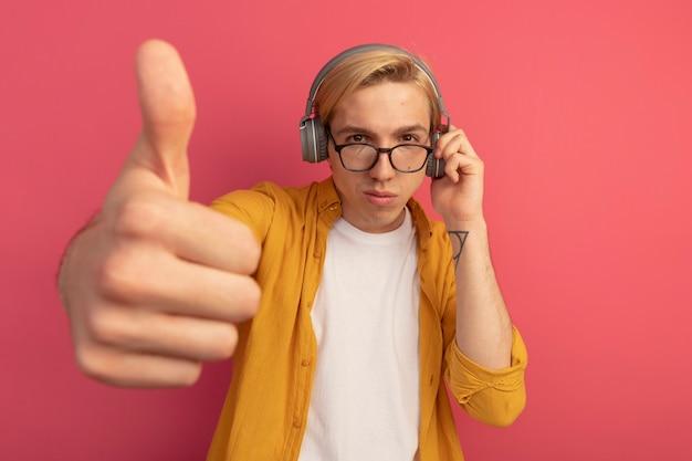 Soddisfatto giovane ragazzo biondo che indossa maglietta gialla e occhiali con le cuffie che mostra il pollice in alto isolato sul rosa