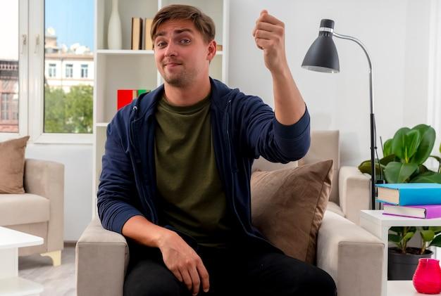 満足している若いブロンドのハンサムな男は、リビングルーム内のカメラを見ながら拳を上げて肘掛け椅子に座っています