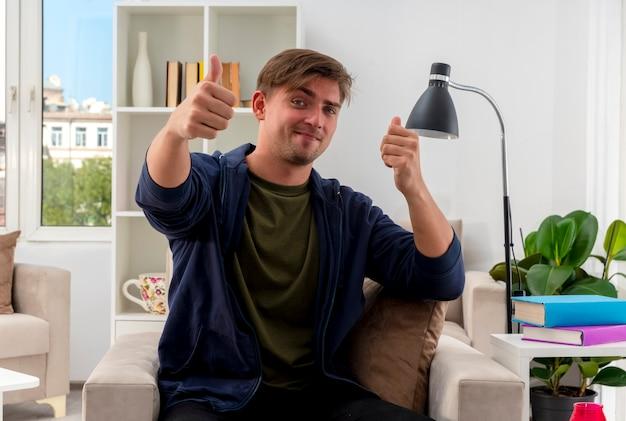 기쁘게 젊은 금발의 잘 생긴 남자는 거실 안에 두 손으로 안락의 자 엄지 손가락에 앉아