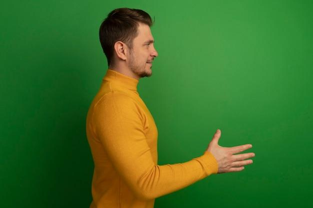 Довольный молодой блондин красавец, стоящий в профиль, смотрит прямо, делая приветственный жест, изолированный на зеленой стене с копией пространства
