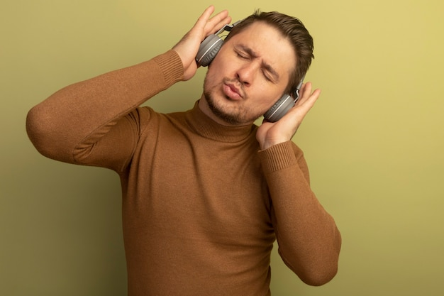 Pleased young blonde handsome man wearing headphones putting hands on them listening to music with closed eyes isolated on olive green wall with copy space