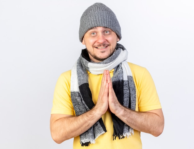 Довольный молодой блондин больной в зимней шапке и шарфе держит руки вместе, изолированные на белой стене