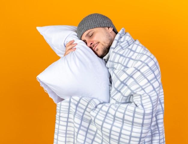 Довольный молодой блондин больной в зимней шапке и шарфе, завернутый в плед, держит и кладет голову на подушку, изолированную на оранжевой стене