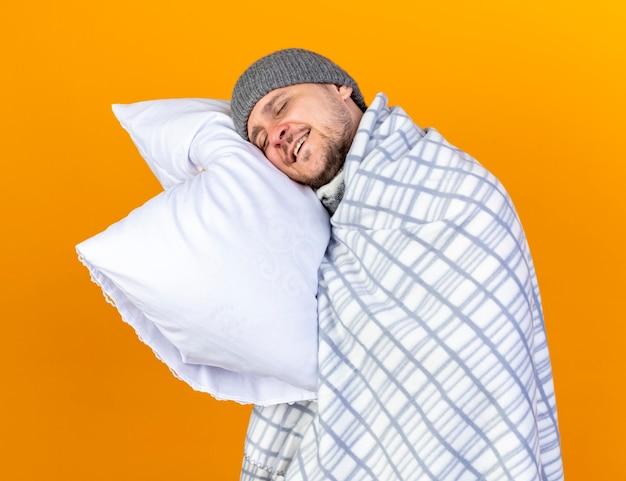 Довольный молодой блондин больной в зимней шапке, завернутый в клетчатые трюмы, кладет голову на подушку, изолированную на оранжевой стене