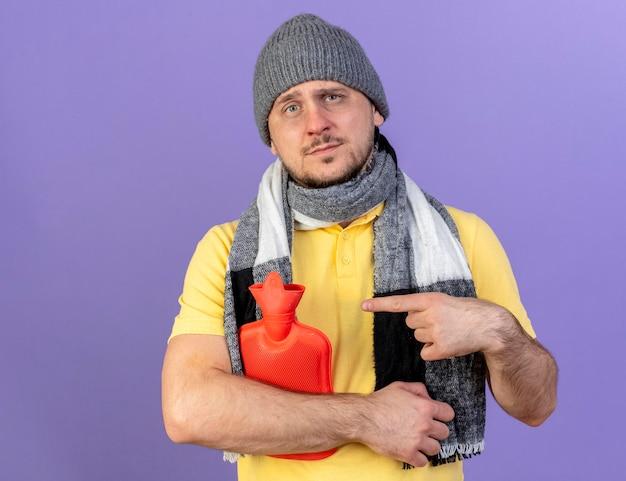 冬の帽子とスカーフを身に着けている若い金髪の病気のスラブ人を喜ばせる