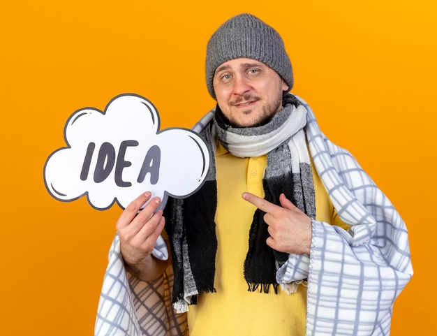 Pleased young blonde ill slavic man wearing winter hat and scarf wrapped in plaid holds and points at idea bubble isolated on orange wall with copy space