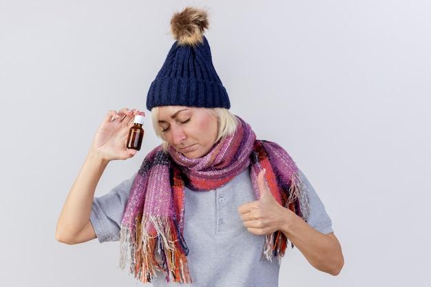 冬の帽子とスカーフを身に着けている幸せな若い金髪の病気のスラブ女性は、ガラス瓶に薬を保持し、コピースペースで白い壁に隔離された親指を立てる
