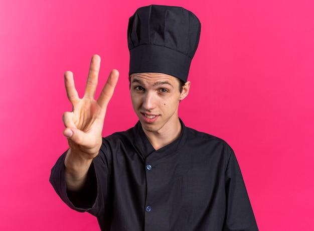 シェフの制服とキャップで手で3つを示す満足している若いブロンドの男性料理