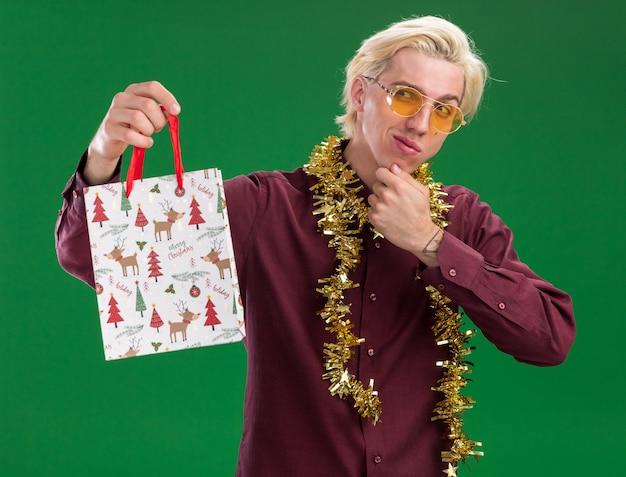 Довольный молодой блондин в очках с гирляндой из мишуры на шее, держащий рождественский подарочный пакет, глядя в сторону, касаясь подбородка, изолированного на зеленой стене