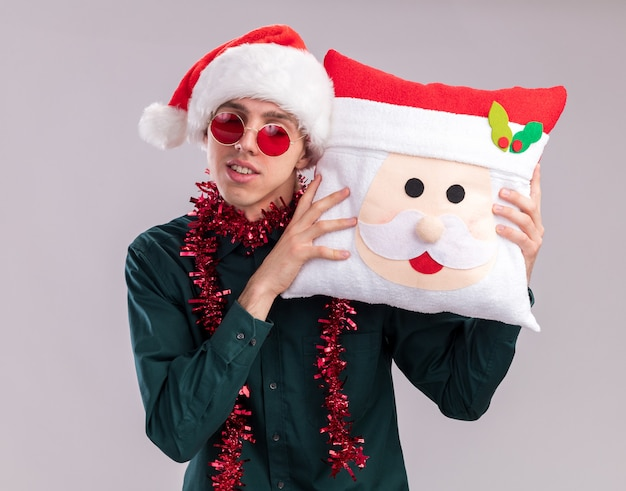 Pleased young blonde man wearing santa hat and glasses with tinsel garland around neck holding santa claus pillow touching head with it with closed eyes isolated on white background